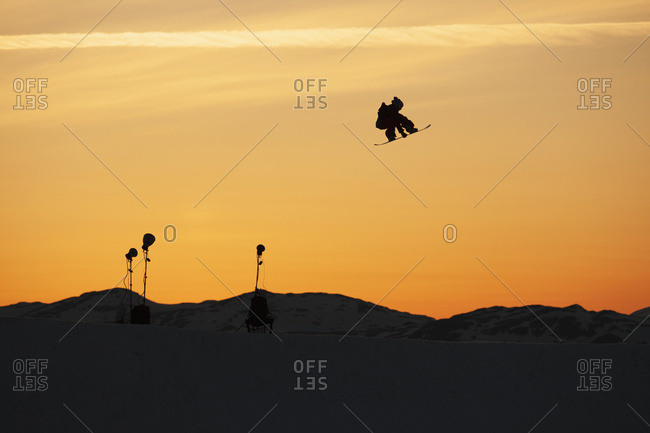 Silhouette Of A Snowboarder Jump In Mid-Air At Sunset; Norway