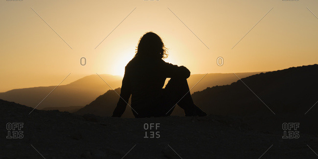 Silhouette Of A Woman Sitting With A View Of The Hilly Landscape Of Valle De La Luna At Sunset; San Pedro De Atacama, Antofagasta Region, Chile