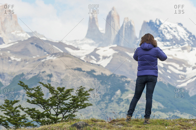 A Woman Stands With A View Of The Rugged Mountain Landscape, Torres Del Paine National Park; Torres Del Paine, Magallanes And Antarctica Chilena Region, Chile