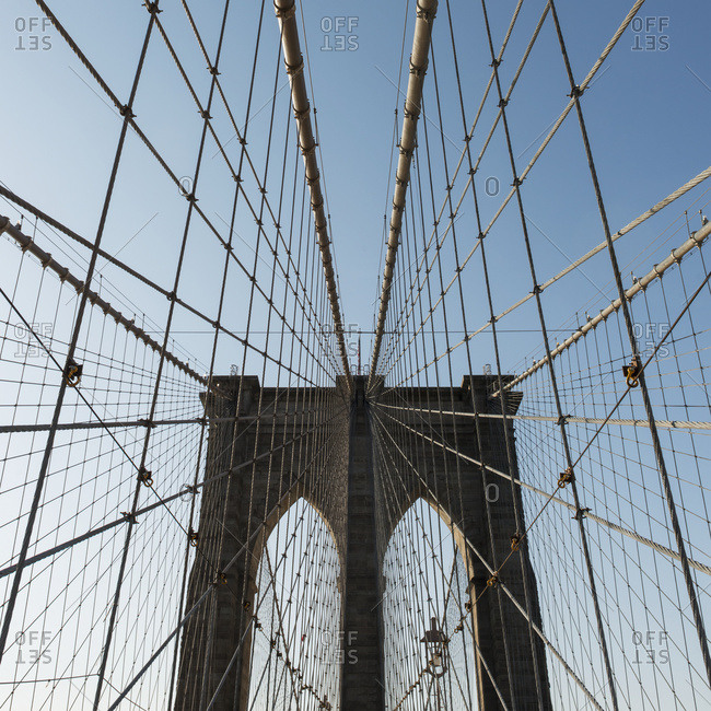 Pattern Of The Cables On A Bridge Against A Blue Sky; New York City, New York, United States Of America