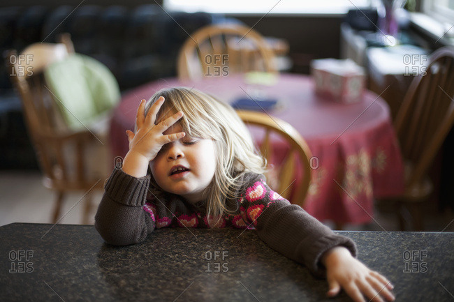 Young Girl Sitting At The Kitchen Counter With A Cute Expression; Surrey, British Columbia, Canada