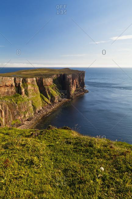 Cliff Along The Coastline And View Of The Ocean And Blue Sky; Orkney, Scotland