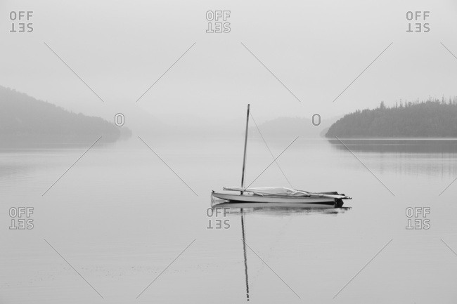 Solitary Sailboat Reflected In A Misty Calm Lake; Ontario, Canada