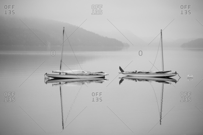 Two Sailboats Reflected In A , Misty Lake; Ontario, Canada