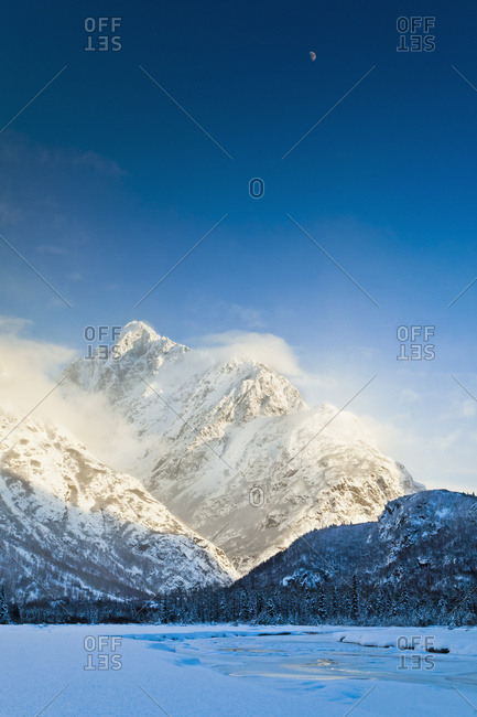 Crescent Moon Above Snow Covered Chugach Mountains And The Frozen Eagle River, Chugach State Park, South-central Alaska, Winter.