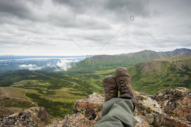 POV Of Hikers Legs And Feet As He Rests And Enjoys The View From Flat Top Mountain Overlooking The Anchorage Bowl, South-central Alaska, Summer