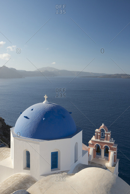 A Blue Domed Church And Pink Bell Tower Overlooking The Caldera; Oia, Santorini, Cyclades, Greek Islands, Greece