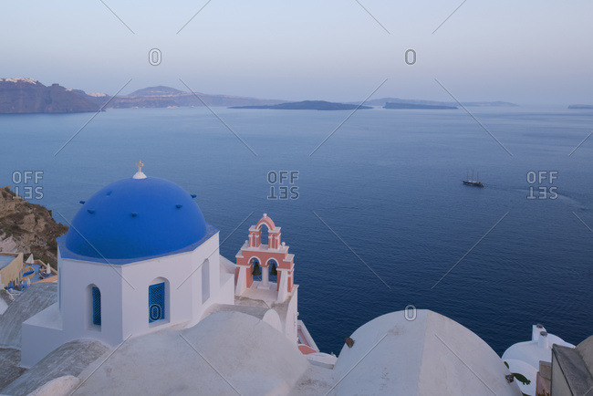 A Blue Domed Church And Pink Bell Tower Overlooking The Caldera At Dusk; Oia, Santorini, Cyclades, Greek Islands, Greece