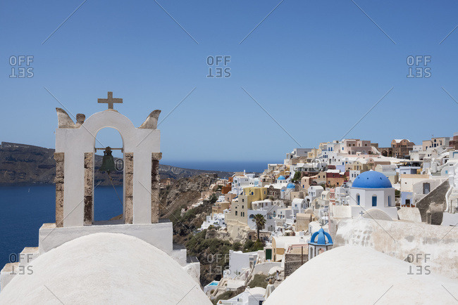 A Church Bell Tower And Traditional Painted Houses Overlooking The Caldera; Oia, Santorini, Cyclades, Greek Islands, Greece