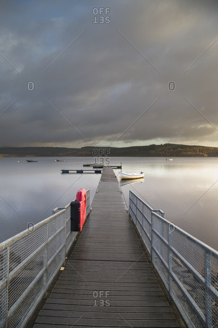 A Wooden Dock With White Metal Railing Leading Out To A Tranquil Lake With Clouds At Sunset; Kielder, Northumberland, England