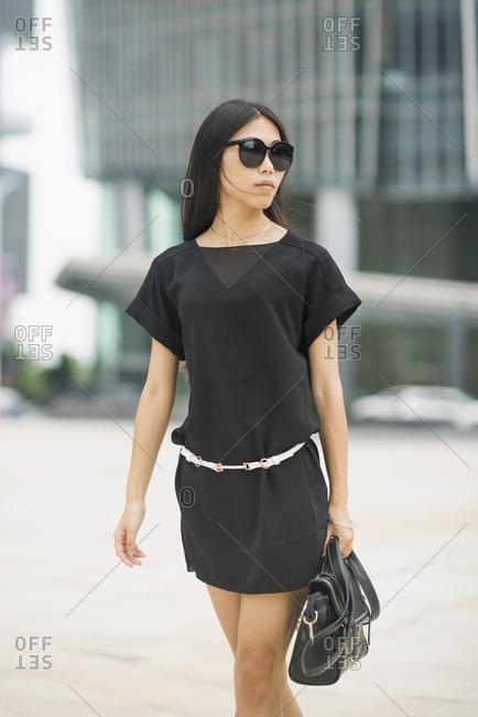 Young Woman Walking In Business District; Xiamen, China