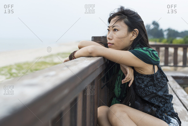 A Young Woman Sits Against A Wooden Railing Looking Out At The Ocean; Jincheng, Kinmen, Taiwan