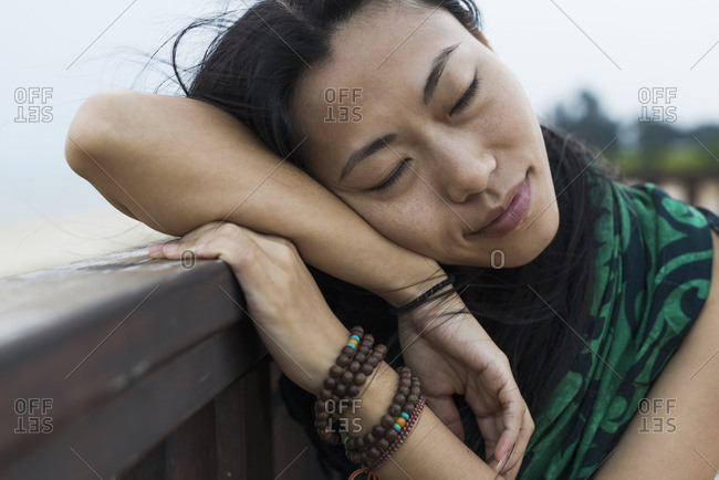 A Young Woman Lays Her Head Against A Wooden Railing At The Beach; Jincheng, Kinmen, Taiwan