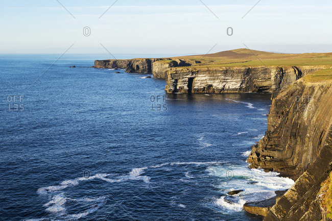 Dramatic Rock Cliffs Along The Shoreline At Sunset With Blue Sky; Kilkee, County Clare, Ireland