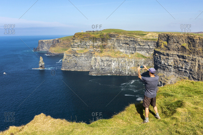 Man Standing On Grassy Cliff's Edge Overlooking Large Sea Stack Rock Structure In The Ocean With Boat Taking A Photo With Phone; Liscannor, County Clare, Ireland