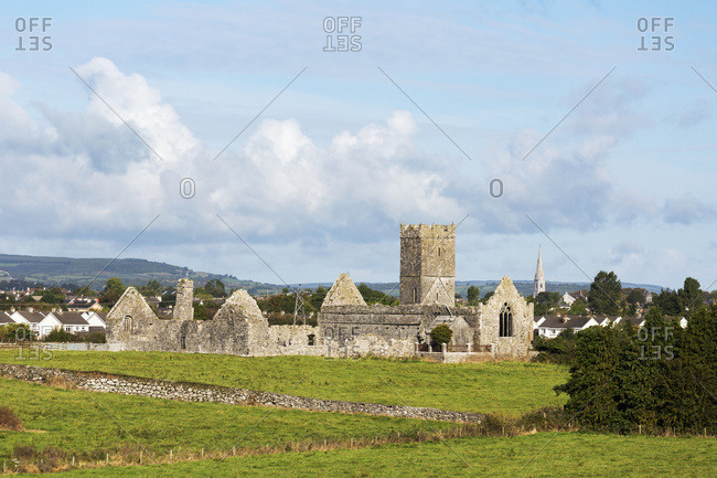 Old Stone Ruin With Church Tower And Roofless Buildings With Clouds And Blue Sky; Ennis, County Clare, Ireland
