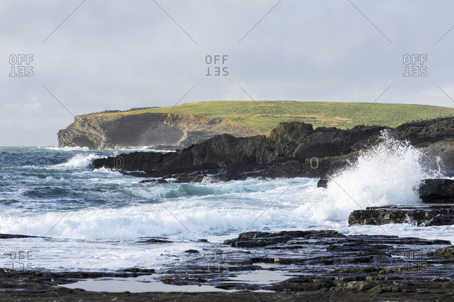 Waves Crashing Into Rocky Coast With Large Grassy Hill And Cliffs In Background; Kilkee, County Clare, Ireland