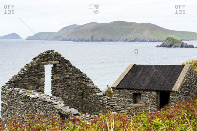 Roofless Stone Building And Roofed Stone Building Overlooking The Bay With Islands In The Background; Dingle, County Kerry, Ireland