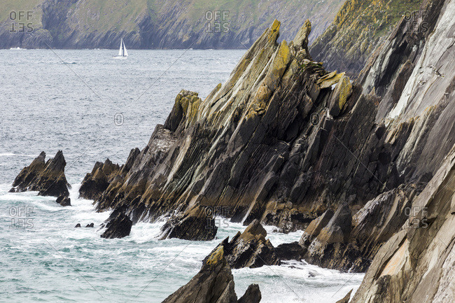 Rugged Rocky Shoreline With Sailboat In The Distance; Dingle, County Kerry, Ireland