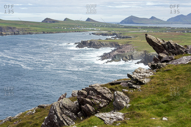 Rugged Rocks In The Hillside Overlooking Rough Coastline And Flat Grasslands And Mountains In The Distance; Ballinglanna, County Cork, Ireland