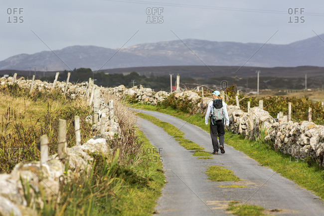 Female Hiker Walking Along The Road Framed With Stone Fences And Mountains In The Distance; Omey Island, County Galway, Ireland