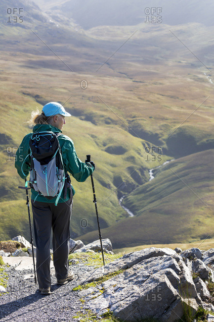 Female Hiker On Rock Trail Overlooking Grassy River Valley Below; Letterfrack, County Galway, Ireland