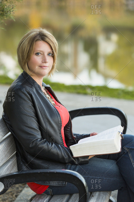 Mature Christian Woman Studying Her Bible In A City Park Setting Beside A Lake; Edmonton, Alberta, Canada