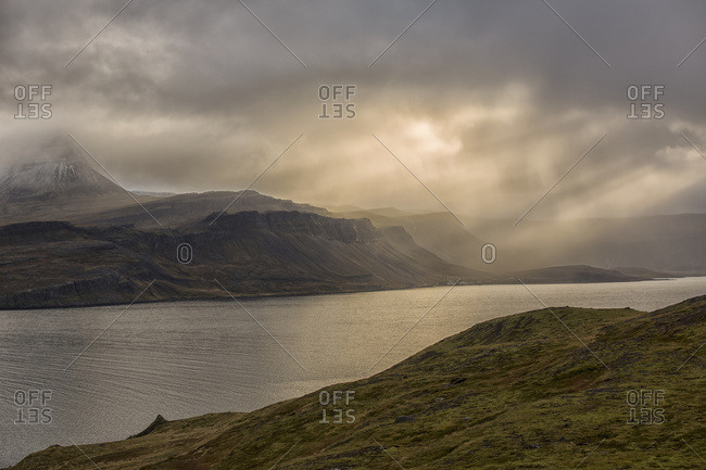 Beams Of Light Shine Down On The Mountains And Abandoned Village Of Djupavik; Iceland