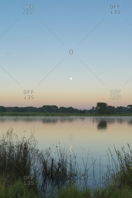 Moon Setting Over The Shire River At Dawn, Liwonde National Park; Malawi
