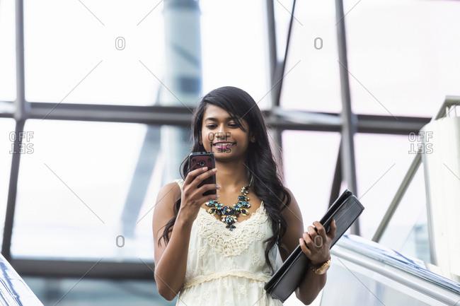 Young Professional Businesswoman Texting On Her Smart Phone On Escalator; Edmonton, Alberta, Canada