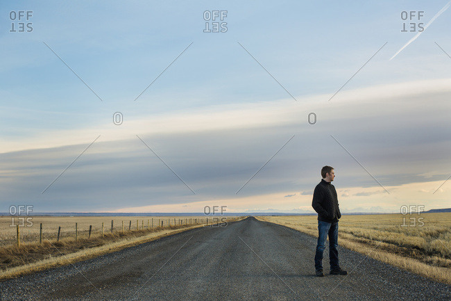 Man Standing On A Rural Road; Claresholm, Alberta, Canada
