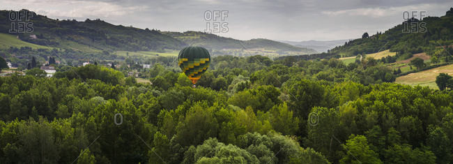 A Hot Air Balloon Flies Low Over A Spring Valley Landscape; Tuscany, Italy