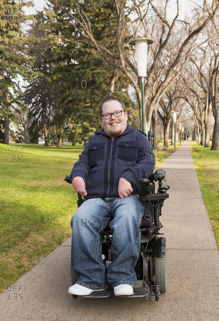 Disabled Man Using His Powered Wheelchair In A Park In Autumn; Edmonton, Alberta, Canada