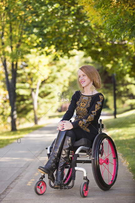 Young Paraplegic Woman In Her Wheelchair On A Path In A City Park In Autumn; Edmonton, Alberta, Canada