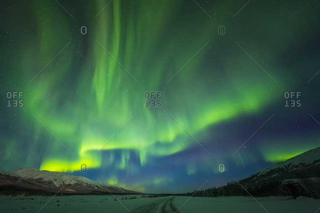 The Aurora Borealis Glows Over The Frozen Richardson Highway On A Bitterly Cold Night Near Black Rapids In The Alaska Range; Alaska, United States Of America