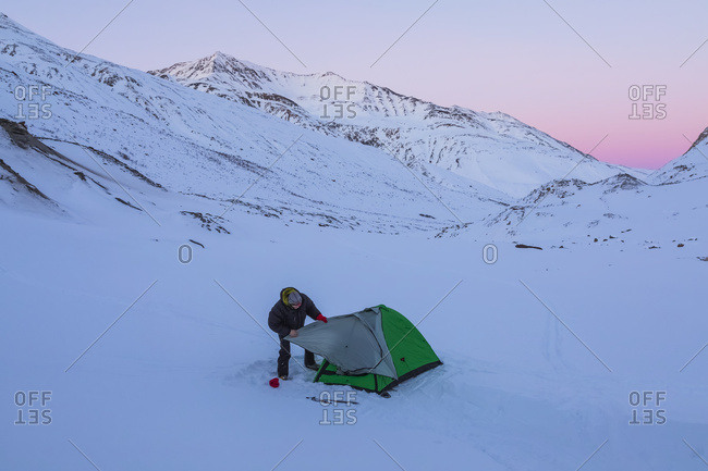 A Man Assembling A Tent After Sunset During A Winter Camping Trip In The Alaska Range, Near Augustana Glacier; Alaska, United States Of America
