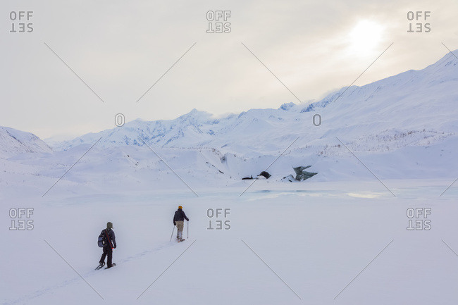 Two Snowshoers Approach Canwell Glacier In The Alaska Range On A Winter Day; Alaska, United States Of America