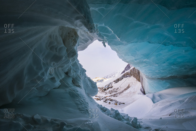 A Wave-Like Formation Of Snow Curls Around The Entrance Of A Small Ice Cave In The Moraine Of Black Rapids Glacier In Winter; Alaska, United States Of America