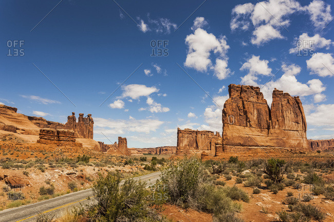 Rugged Rock Formations And Shrubs In The Desert, With A Road Passing Through; Arizona, United States Of America
