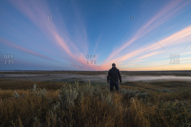 A Man Stands Watching  The Sunrise Color Over The Frenchman River Valley In Grasslands National Park; Saskatchewan, Canada