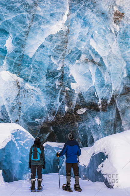 A Couple Of Snowshoers Examine A Large Blue Wall Of Ice With Several Collapsed Pieces Of Ice At The Bottom At The Terminus Of Canwell Glacier In The Alaska Range; Alaska, United States Of America