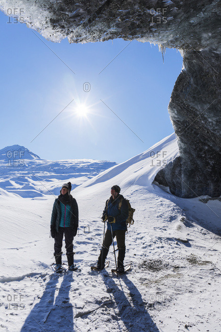 A Couple Snowshoeing And Standing Beneath The Entrance To An Ice Cave On A Sunny Winter Day At Canwell Glacier In The Alaska Range; Alaska, United States Of America