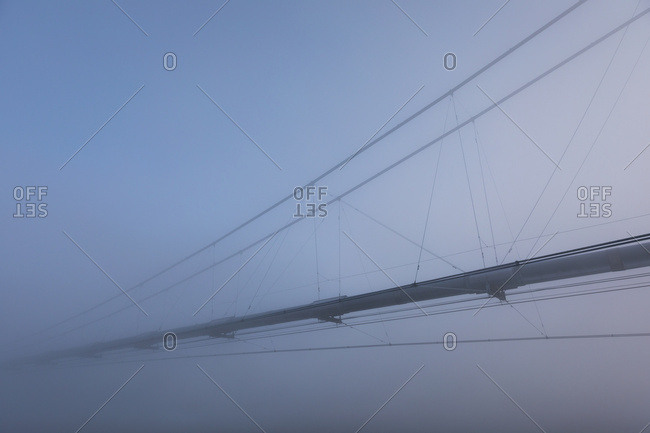 The Trans-Alaska Pipeline Appears Through Fog Where It Crosses The Tanana River On A Subzero Morning; Alaska, United States Of America