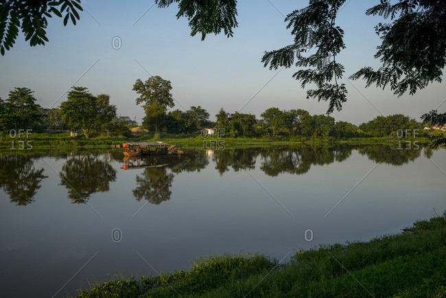 A Tranquil Scene With Trees Reflected In The River Water And A Blue Sky; Chiang Rai, Thailand