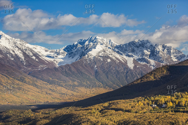 Eagle River Valley, Homes Nestled Among The Trees In The Foreground, Autumn Coloured Trees Filling The Valley, Snow Covering The Chugach Mountains In The Background, Eagle River, South-Central Alaska; Alaska, United States Of America