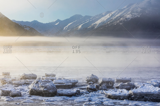 The Sun Shines Through Low Altitude Fog Cast In Warm Light Along Turnagain Arm And The Seward Highway, Sea Ice Covering The Ocean In The Foreground, The Kenai Mountains Revealed In The Background, South-Central Alaska; Alaska, United States Of America