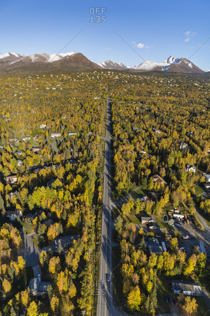 Aerial View Of The Hillside Neighborhood Homes In Anchorage, Snow Covering The Peaks Of The Chugach Mountains In The Background, Autumn Coloured Trees Filling The City, South-Central Alaska; Alaska, United States Of America