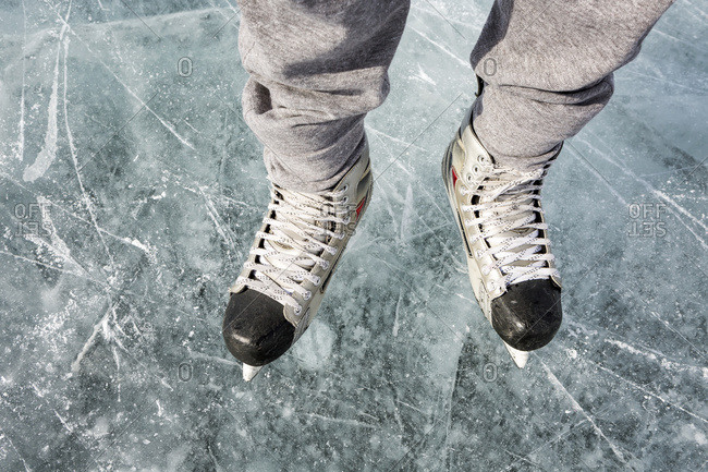 High Angle View And Close-Up Of Hockey Skates On Ice; Calgary, Alberta, Canada
