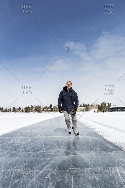 Man Skating On Freshly Groomed Ice On Lake With Houses In The Background And Blue Sky; Calgary, Alberta, Canada