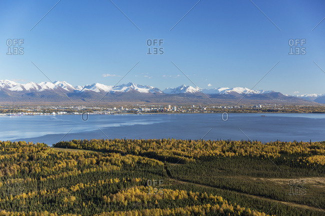 View Of Downtown Anchorage, Point Mackenzie In The Foreground, The Snow Covered Chugach Mountains In The Distance, South-Central Alaska; Anchorage, Alaska, United States Of America